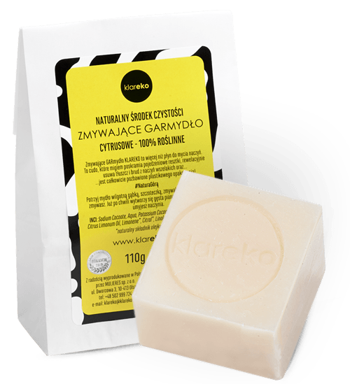 Dishwashing bar soap is square bar of a natural color packaged in a paper bag.