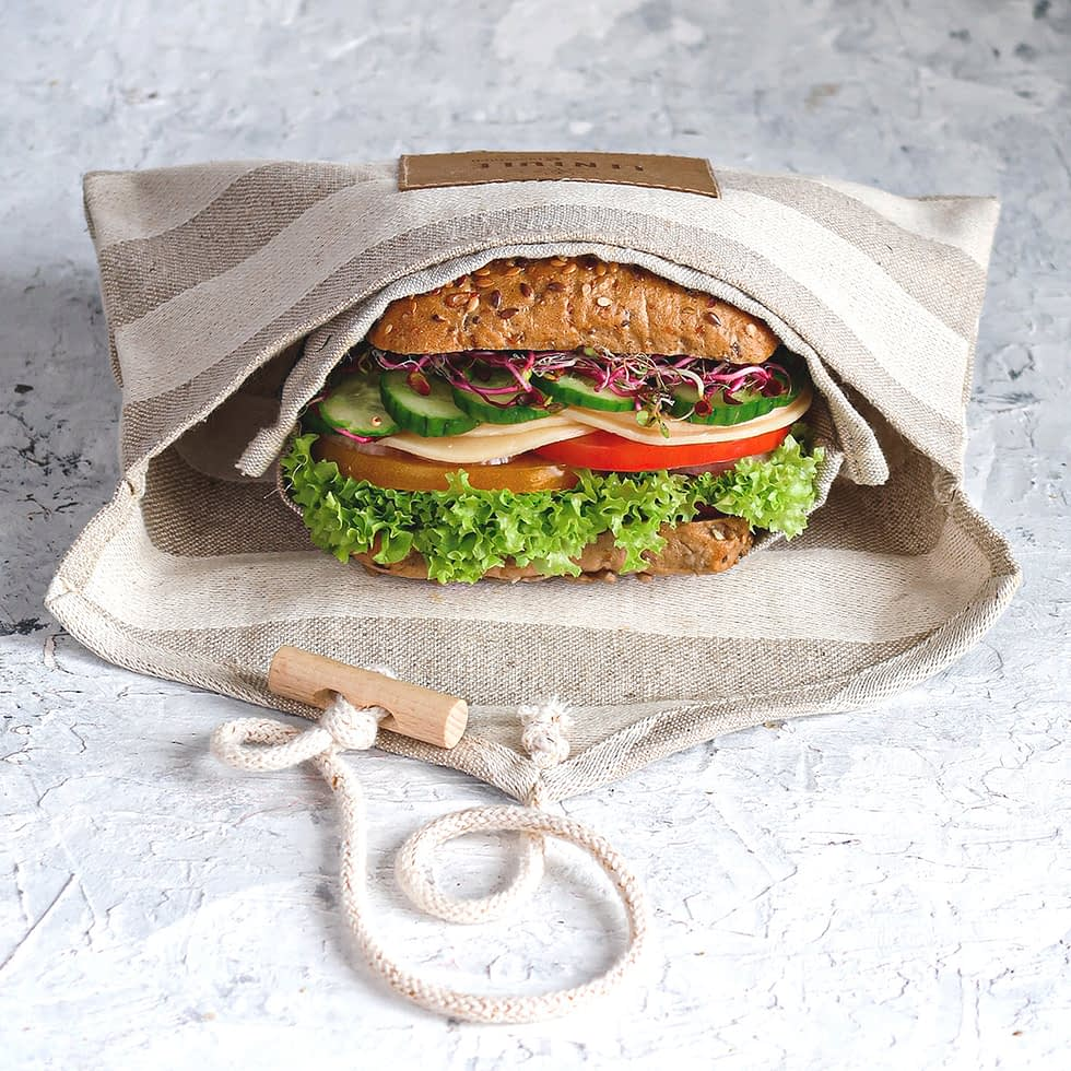 Lentule linen sandwich wrap. Inside, a juicy sandwich with lettuce, tomato and cheese.